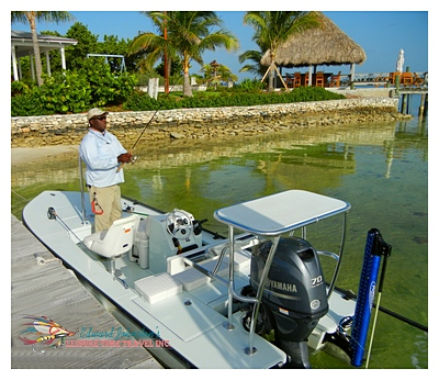 Joseph Pinder with AJ's dockside Tiki Bar in background at Deep Water Cay